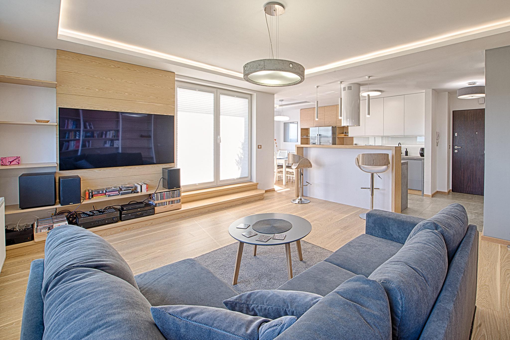 Salon podzielony jest na trzy strefy funkcjonalne: przestrzeń rekreacyjną, kuchnię oraz jadalnię.