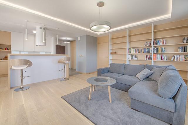 Tylna ściana salonu została zagospodarowana jako obszerny regał na książki, z ukrytymi drzwiami do części prywatnej mieszkania.
