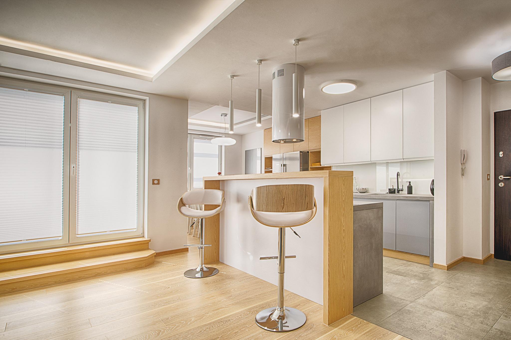 Strefa kuchenna oddzielona jest od salonu wyspą z wysokim drewnianym barem.