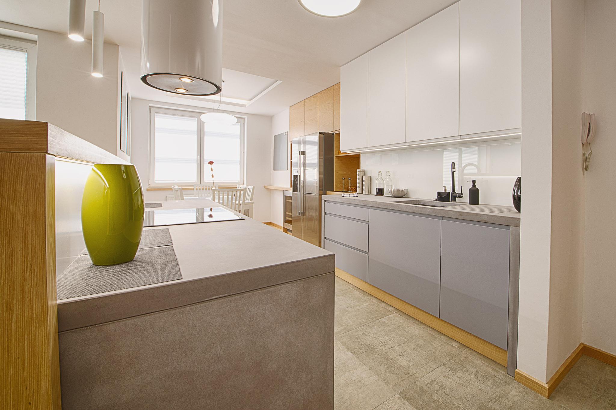 W kuchni zastosowaliśmy surowe materiały: beton, gres i lakierowane fronty, które kontrastują z ciepłymi, drewnianymi listwami przypodłogowymi i cokołami.